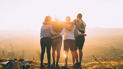 backlit image of four people standing together with their backs to the camera